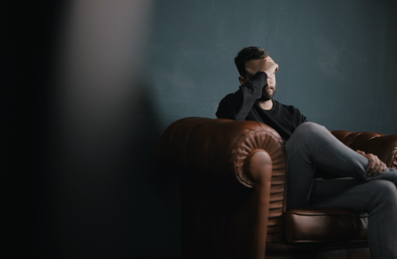 A man, clearly worried, sitting on a couch.